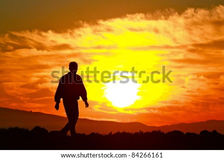 A silhouette of a man walking on a trail at sunrise - stock photo