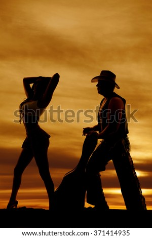 A silhouette of a man with a guitar and cowboy hat behind a woman. - stock photo