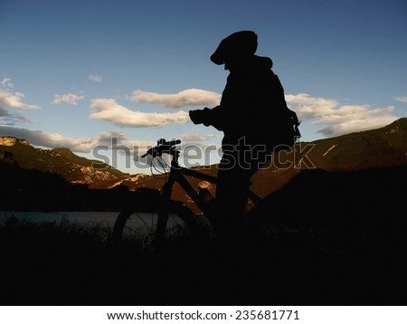 A silhouette of a mountain biker