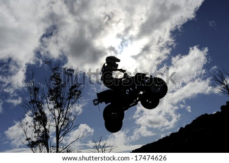A silhouette of a quad bike (ATV) jumping through a cloudy sky