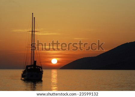 A silhouette of a sailboat in the sunset