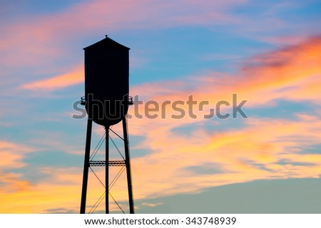 A silhouette of a small town water tower against a brilliant early morning sky. - stock photo