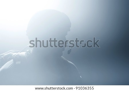 A silhouette of a soldier in the smoke after the explosion - stock photo