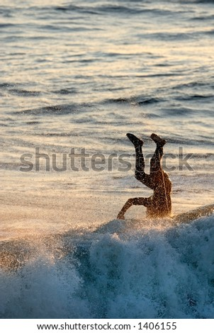 A silhouette of a surfer landing head first into the water. - stock photo