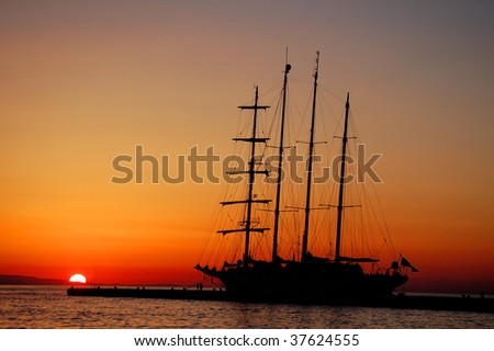 A silhouette of a tall ship with the setting sun.