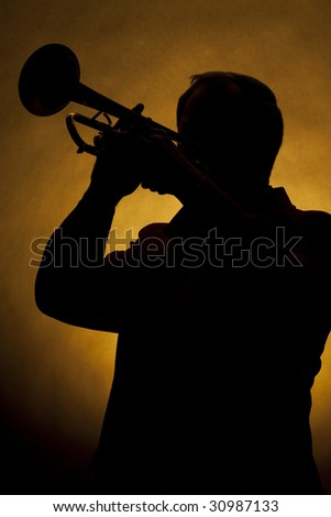 A silhouette of a trumpet being played by a trumpet player in the vertical format with copy space and a gold background. - stock photo