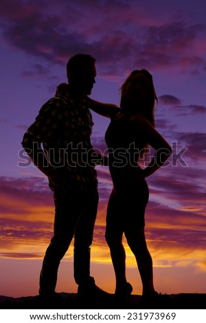 a silhouette of a woman and her man in the outdoors.