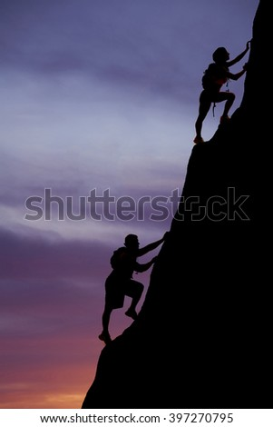 A silhouette of a woman and man climbing up a mountain with packs on their backs. - stock photo