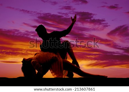 A silhouette of a woman and man doing a dance move in the outdoors. - stock photo