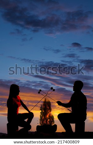 A silhouette of a woman and man in the outdoors roasting marshmallows over a fire. - stock photo