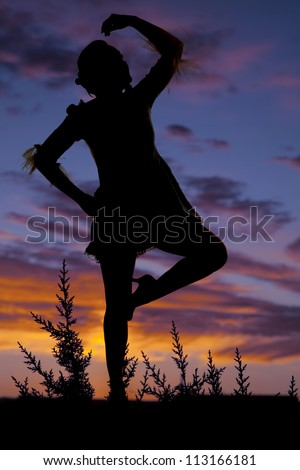 A silhouette of a woman dancing with a colorful sky behind her. - stock photo