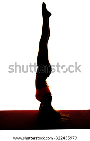 a silhouette of a woman doing a headstand with legs straight up. - stock photo
