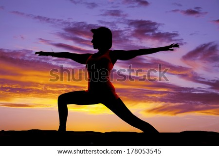 a silhouette of a woman doing a yoga pose warrior one.