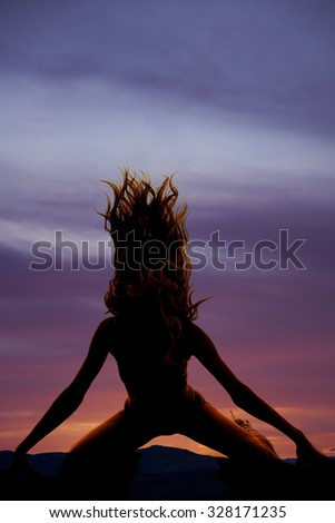 A silhouette of a woman flipping her hair kneeling.