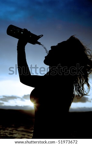 A silhouette of a woman getting refreshed by pouring water into her mouth from her water bottle
