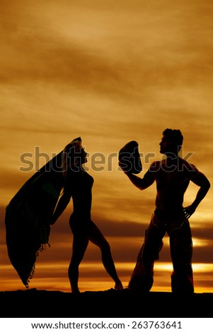 A silhouette of a woman holding her sarong in the air with the wind blowing.  Her cowboy taking off his hat for her. - stock photo