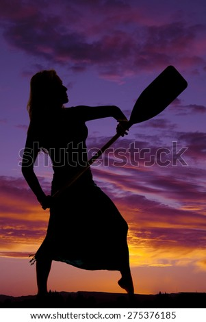 A silhouette of a woman holding on to a paddle in the outdoors. - stock photo