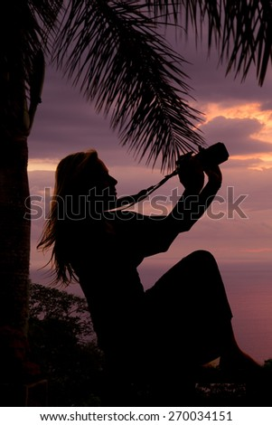 A silhouette of a woman holding on to her camera, sitting by a palm tree. - stock photo