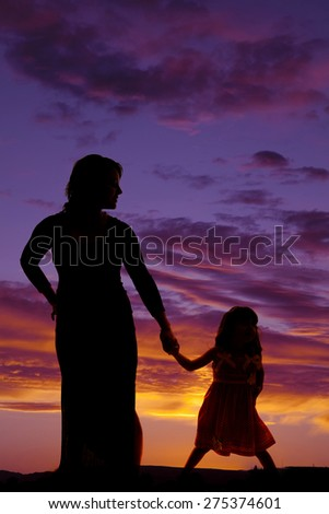 a silhouette of a woman holding on to her daughters hands in the outdoors. - stock photo
