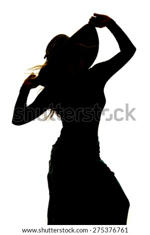 a silhouette of a woman holding on to her hat with the wind blowing her hair. - stock photo