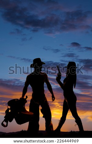 a silhouette of a woman holding on to her pistol, standing by her cowboy who is holding on to a saddle. - stock photo