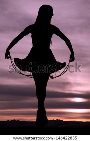 a silhouette of a woman holding on to her skirt - stock photo