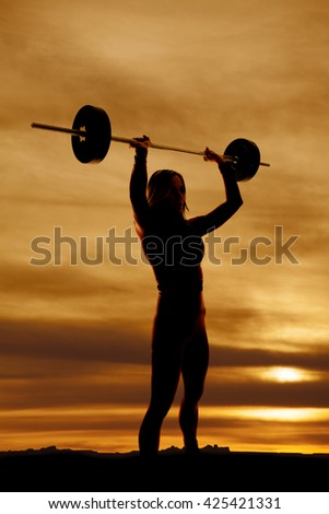 A silhouette of a woman holding onto a barbell over her head - stock photo