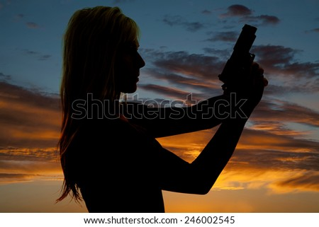 a silhouette of a woman holding onto a pistol looking forward. - stock photo