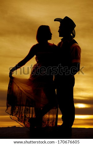 A silhouette of a woman holding out her dress with her cowboy looking at her. - stock photo