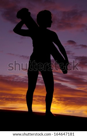 A silhouette of a woman holding something looking to the side. - stock photo