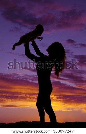 A silhouette of a woman holding up her baby girl. - stock photo