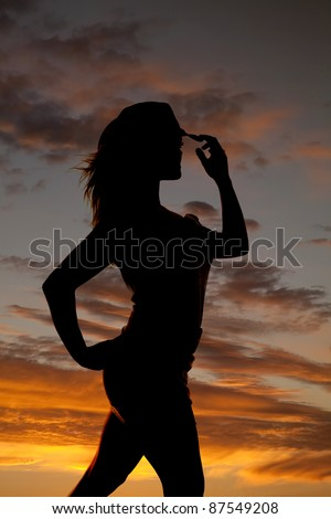 A silhouette of a woman in front of a beautiful sunset touching her hat. - stock photo