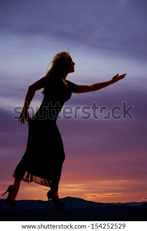 A silhouette of a woman in her dress and high heels reaching out looking to the side. - stock photo