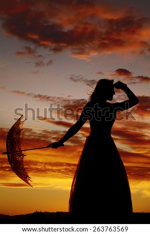 A silhouette of a woman in her dress hanging on to her umbrella. - stock photo