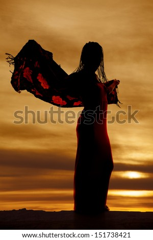 a silhouette of a woman in her dress with her sarong blowing in the wind. - stock photo
