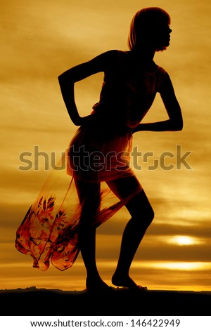 a silhouette of a woman in her flowing dress looking to the side - stock photo