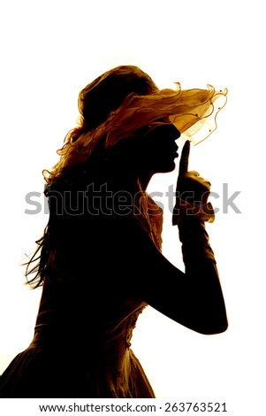 A silhouette of a woman in her formal dress with her finger up to her mouth, telling someone to be quiet. - stock photo