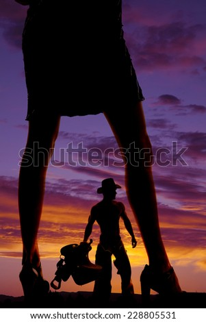 A silhouette of a woman in her heels , watching her cowboy holding on to his saddle. - stock photo