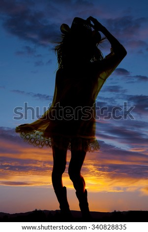 A silhouette of a woman in her western hat and boots, with a beautiful sky behind her. - stock photo