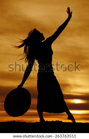 A silhouette of a woman in paradise in her skirt, holding on to her hat. - stock photo