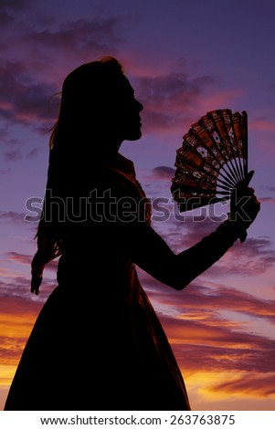A silhouette of a woman in the outdoors, holding on to her lace fan. - stock photo