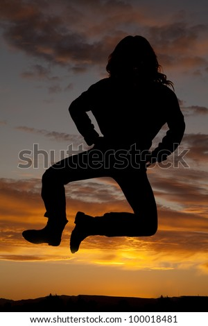 A silhouette of a woman jumping up in the colorful sky. - stock photo