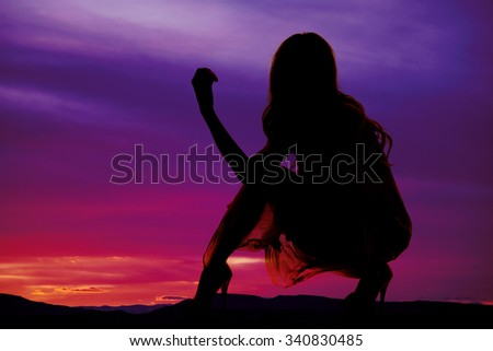 A silhouette of a woman kneeling down in her sheer dress and heels. - stock photo