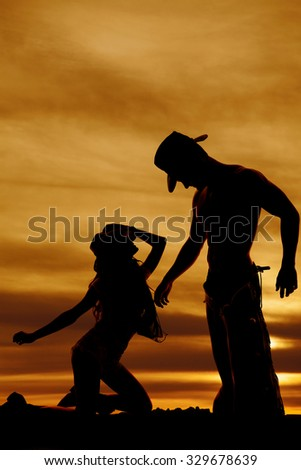 A silhouette of a woman kneeling in front of her cowboy. - stock photo
