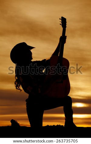 a silhouette of a woman kneeling with her guitar. - stock photo