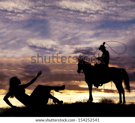 A silhouette of a woman laying on the ground reaching out to a cowboy on a horse.