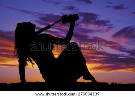 a silhouette of a woman leaning back holding up her camera. - stock photo