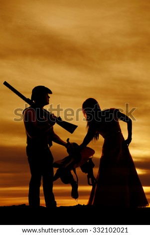 A silhouette of a woman leaning over and touching her cowboys saddle. - stock photo