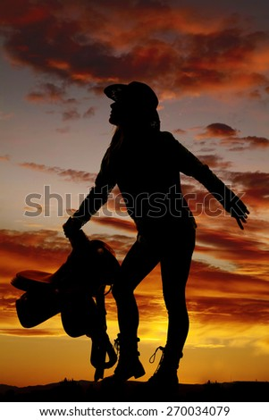 A silhouette of a woman leaning over holding on to her saddle.