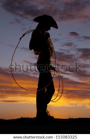 A silhouette of a woman looking down at the ground holding on to her rope